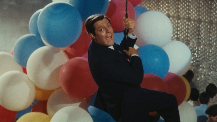 mies roikkuu köydestä ilmapallojen keskellä