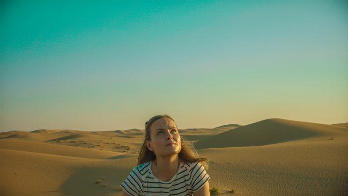 Nainen katselee taivasta aavikolla